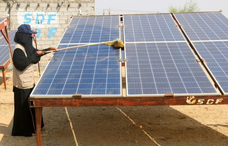 A Yemeni woman cleans a solar panel at the Friends of the Environment Station