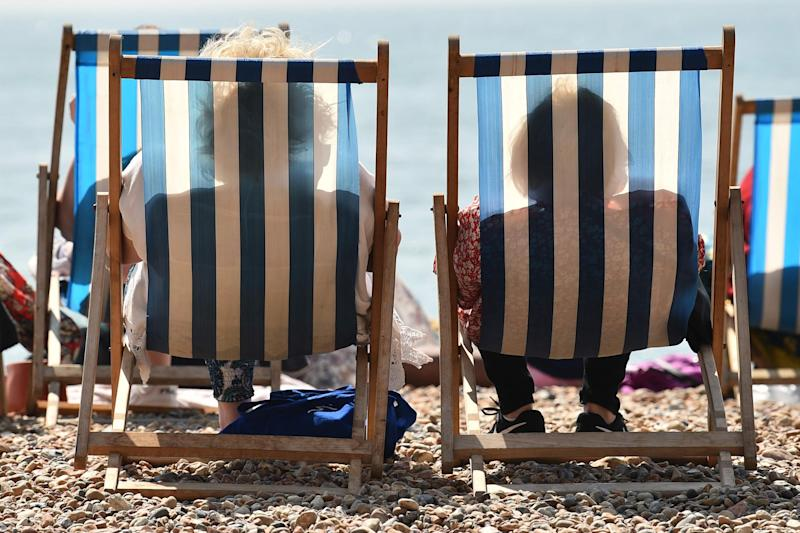 Beach goers relax by the sea in Brighton (AFP/Getty Images)