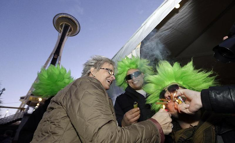 Jeremy Cooper, right, is helped by friends Cecilia Sivertson, left, and David DesRoaches in lighting up three joints at once at a pot party at the Seattle Center Friday, Dec. 6, 2013, in Seattle. Friday marks the first anniversary of the day Washington's legal marijuana law took effect, and hundreds of people celebrated by lighting up near the Space Needle at a party permitted by the city of Seattle. (AP Photo/Elaine Thompson)
