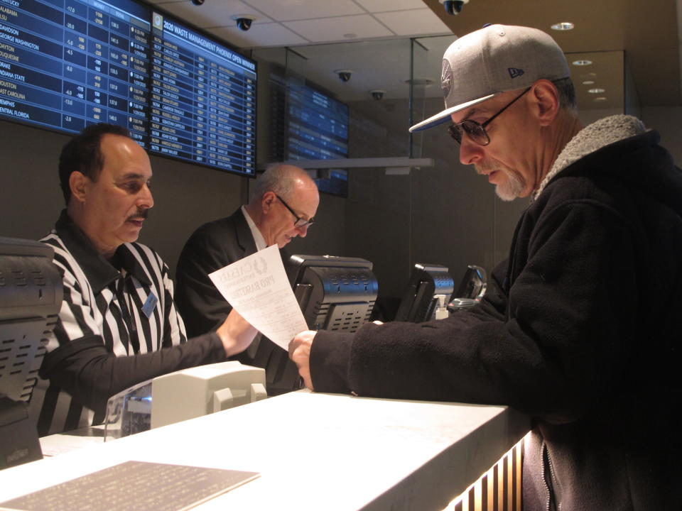 FILE - In this Jan. 29, 2020, file photo, a gambler makes bets on the upcoming Super Bowl at Bally's casino in Atlantic City N.J. The online sports betting company FanDuel will open an in-person sports book at Bally's casino in Atlantic City once the casino's sale to a Rhode Island company is finalized. FanDuel told The Associated Press on Wednesday, Oct. 28, 2020, that it has plans for a temporary sports betting facility in the casino before the end of the year, and will build a permanent sports book on the center of the casino floor next spring. (AP Photo/Wayne Parry, File)