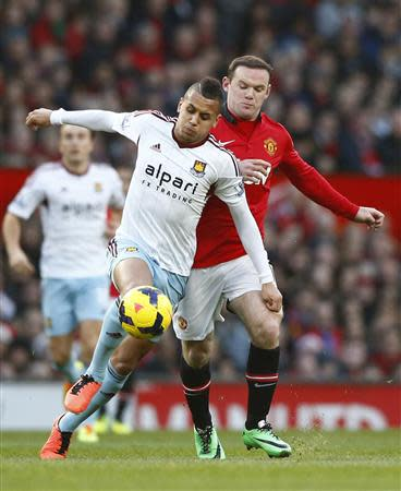 Manchester United's Wayne Rooney (R) challenges West Ham's Ravel Morrison during their English Premier League soccer match at Old Trafford in Manchester, northern England, December 21, 2013. REUTERS/Darren Staples