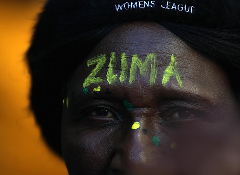 A ruling party African National Congress (ANC) supporter with her forehead painted with President Jacob Zuma's name outside the South Gauteng High Court in Johannesburg, South Africa on Thursday May 24, 2012. President Jacob Zuma is asking the High Court to issue an order that display of the now-defaced painting violates his constitutional right to dignity. The gallery and the artist counter that freedom of expression, also protected by the constitution, is at stake. (AP Photo/Themba Hadebe)