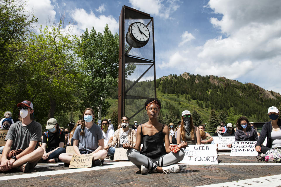 Jenelle Figgins, center, leads a moment of silent meditation before protesters march through the streets of Aspen, Colo., Sunday, May 31, 2020, to demonstrate against the death of George Floyd. Protests were held throughout the country over the death of Floyd, a black man who died after being restrained by Minneapolis police officers on May 25. (Kelsey Brunner/The Aspen Times via AP)
