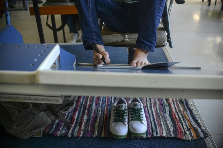 Arijon Krasniqi, a disabled 14-year-old Kosovar, uses his toes to make notes in school; a new study has found that the brain maps each toe in armless artists who paint with their feet but not in handed people