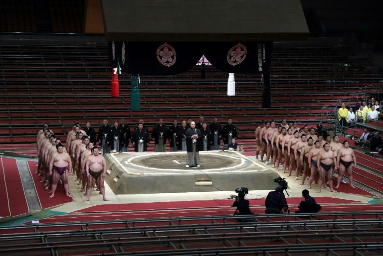 Wrestlers and officials line up before the start of the spring grand tournament held behind closed doors in Osaka