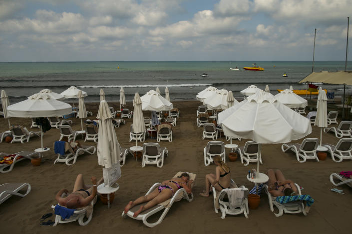Tourists sunbathing at the beach of Antalya , southern Turkey, on Sunday, June 20, 2021. Hotels in Turkey's Antalya region, a destination beloved by holidaymakers, are preparing to finally resume operations as they expect the return of international tourists after months of setbacks caused by the pandemic that halted travel. (AP Photo/Emrah Gurel)