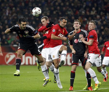 Bayer Leverkusen's Emir Spahic (L) is challenged by Manchester United's Wayne Rooney (2nd L) and Ryan Giggs (3rd L) during their Champions League Group A soccer match at the BayArena in Leverkusen November 27, 2013. REUTERS/Ina Fassbender
