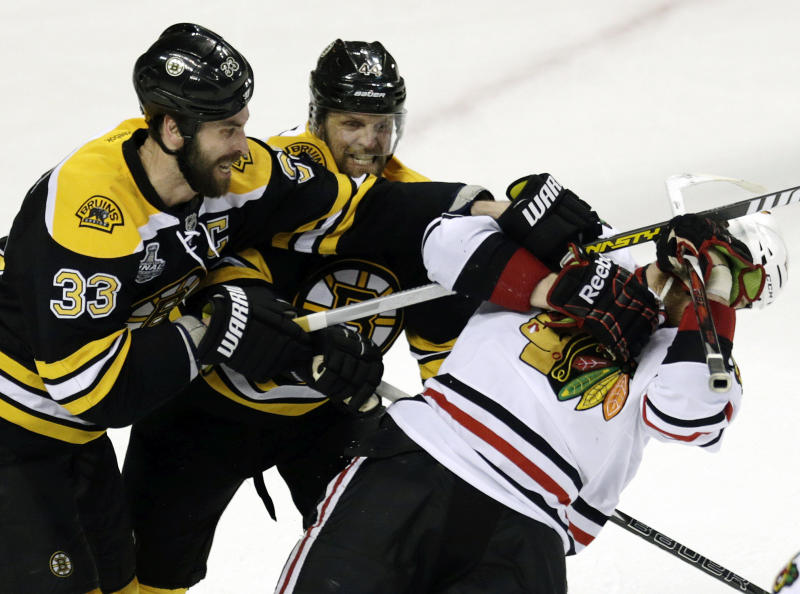Boston Bruins defenseman Zdeno Chara (33), of Slovakia, and Boston Bruins defenseman Dennis Seidenberg, center, of Germany, take down Chicago Blackhawks left wing Bryan Bickell, right, during the third period in Game 3 of the NHL hockey Stanley Cup Finals in Boston, Monday, June 17, 2013. The Bruins won 2-0. (AP Photo/Charles Krupa)