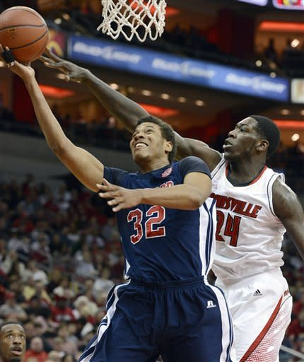 Louisville's Montrezl Harrell, right, attempts to block the shot of Samford's Tim Williams during the first half of an NCAA college basketball game, Thursday, Nov. 15, 2012, in Louisville, Ky. (AP Photo/Timothy D. Easley)