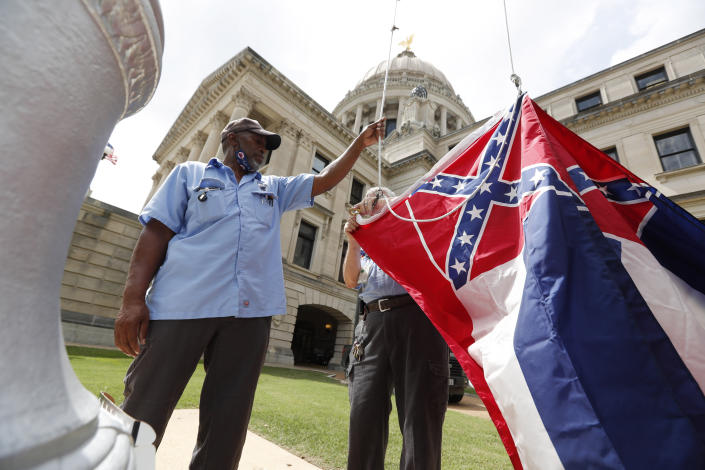 Mississippi Department of Finance and Administration employees Willie Townsend, left, and Joe Brown, attach a Mississippi state flag to the harness before raising it over the Capitol grounds in Jackson, Miss., Tuesday, June 30, 2020. The two men raised about 100 flags, provided by the Secretary of State's office, for people or organizations that purchased a state flag that flew over the grounds. Gov. Tate Reeves will sign a bill Tuesday evening retiring the last state flag with the Confederate battle emblem during a ceremony at the Governor's Mansion. Upon the governor signing the bill, the flag will lose its official status. (AP Photo/Rogelio V. Solis)