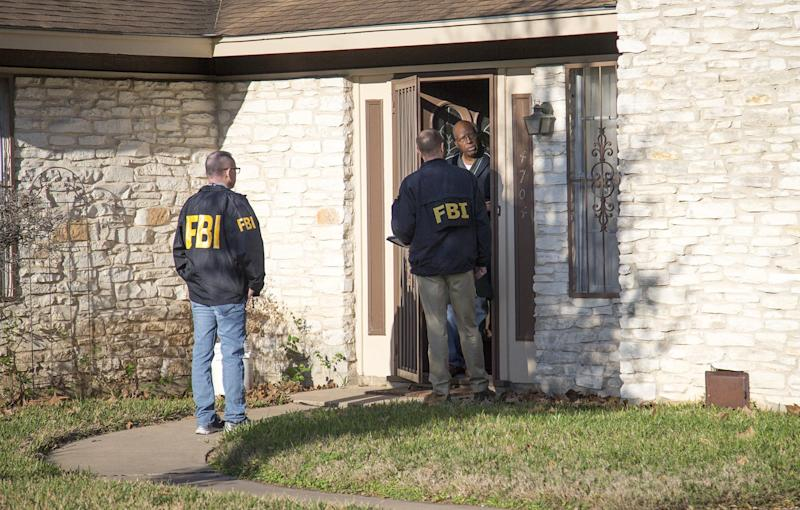 The FBI is pictured investigating the scene in East Austin, Texas, after a teenager was killed by a package explosion: AP