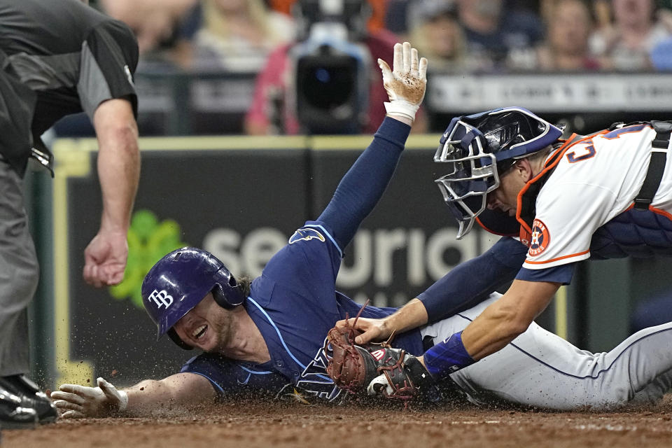 Tampa Bay Rays' Brett Phillips, left, is tagged out at home plate by Houston Astros catcher Jason Castro while trying to stretch a triple into a home run during the eighth inning of a baseball game Wednesday, Sept. 29, 2021, in Houston. (AP Photo/David J. Phillip)