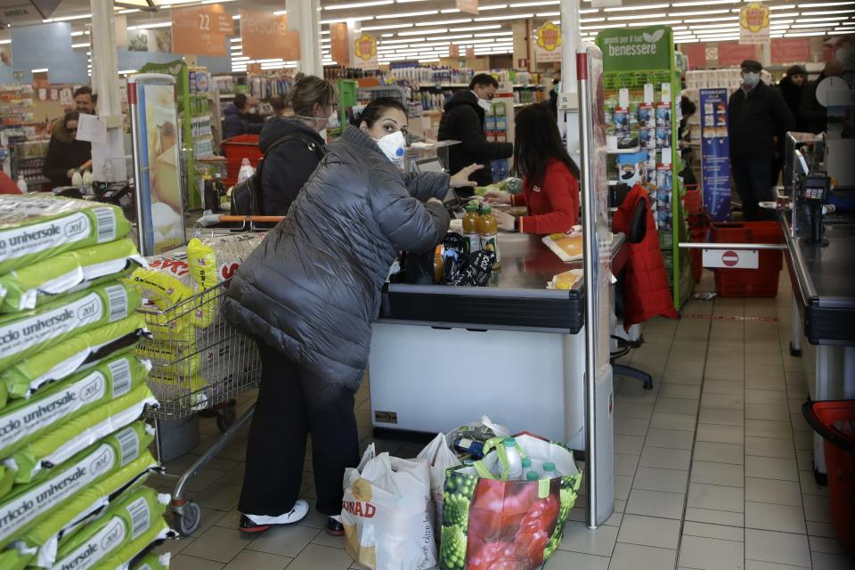 Clients wear sanitary mask in a supermarket in Casalpusterlengo, Italy, Sunday, Feb. 23, 2020. A dozen Italian towns saw daily life disrupted after the deaths of two people infected with the virus from China and a pair of case clusters without direct links to the outbreak abroad. A rapid spike in infections prompted authorities in the northern Lombardy and Veneto regions to close schools, businesses and restaurants and to cancel sporting events and Masses. (AP Photo/Luca Bruno)