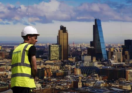 A worker walks past a picture of the London skyline outside the sales office of a property development in central London
