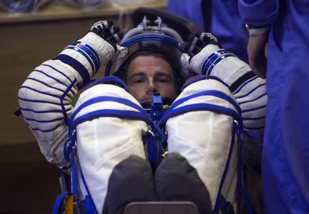 The International Space Station crew member Reid Wiseman of the U.S. looks on during his space suit check at the Baikonur cosmodrome