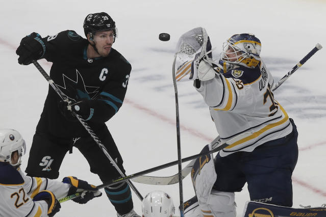 Buffalo Sabres goaltender Linus Ullmark, right, reaches for the puck next to San Jose Sharks center Logan Couture during the third period of an NHL hockey game in San Jose, Calif., Saturday, Oct. 19, 2019. (AP Photo/Jeff Chiu)