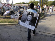 FILE - In this Sept. 21, 2011, file photo, Ricky Jason wears a photograph of James Byrd Jr. outside the Texas Department of Criminal Justice Huntsville Unit before the execution of Lawrence Russell Brewer in Huntsville, Texas. An East Texas town's history as the place where a black man, Byrd, was dragged to death by three white men nearly 21 years ago will again come to the forefront this week as the ringleader responsible for the brutal killing, John William King, is scheduled to be executed. (AP Photo/David J. Phillip, File)