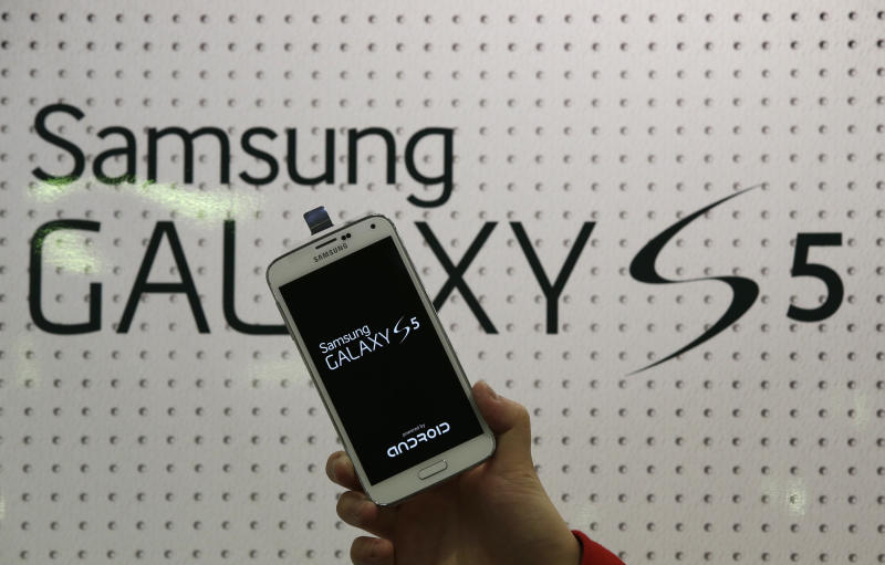 An employee shows Samsung's Galaxy S5 smartphone at a mobile phone shop in Seoul, South Korea, Thursday, March 27, 2014. The global launch of Samsung's latest smartphone is being upstaged by South Korean mobile network companies. SK Telecom, South Korea's largest mobile carrier, said it will start selling the Galaxy S5 on Thursday, two weeks before the scheduled sales launch on April 11. (AP Photo/Lee Jin-man)