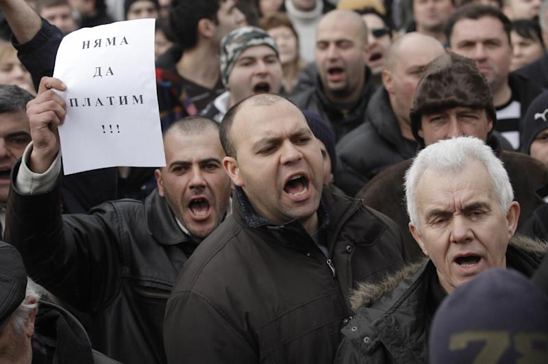 """Bulgarians shout slogans and one holding  a note reading """"We will not pay""""  during a protest against higher electricity and heating bills, in Sofia,  Sunday, Feb. 17, 2013. Thousands of angry Bulgarians chanted """"mafia"""" and """"resignation""""  demanded the expulsion of the three foreign-controlled power distributors that control the local market: Czech Republic's CEZ and Energo-Pro, and Austria's EVN   (AP Photo/Valentina Petrova)"""
