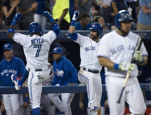 Toronto Blue Jays shortstop Jose Reyes (7) celebrates his solo home run with teammate Jose Bautista, center, as Melky Cabrera, right, approaches the plate against the Boston Red Sox during the sixth inning of a baseball game, Tuesday, July 22, 2014 in Toronto. (AP Photo/The Canadian Press, Nathan Denette)