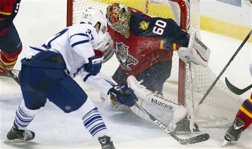 Florida Panthers goalie Jose Theodore (60) stops a shot on goal by Toronto Maple Leafs' Carter Ashton (37) during the first period of an NHL hockey game in Sunrise, Fla., Tuesday, March 13, 2012. (AP Photo/J Pat Carter)