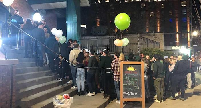 More than 50 people stood in line waiting to get into Harper's in East Lansing, Mich., in late March, despite officials' warnings. Fourteen men and women who visited the brewpub in June have been confirmed to have the coronavirus.