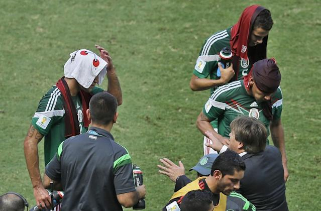 Mexico's head coach Miguel Herrera, bottom, right, talks to his players during a cooling break in the World Cup round of 16 soccer match between the Netherlands and Mexico at the Arena Castelao in Fortaleza, Brazil, Sunday, June 29, 2014. (AP Photo/Themba Hadebe)