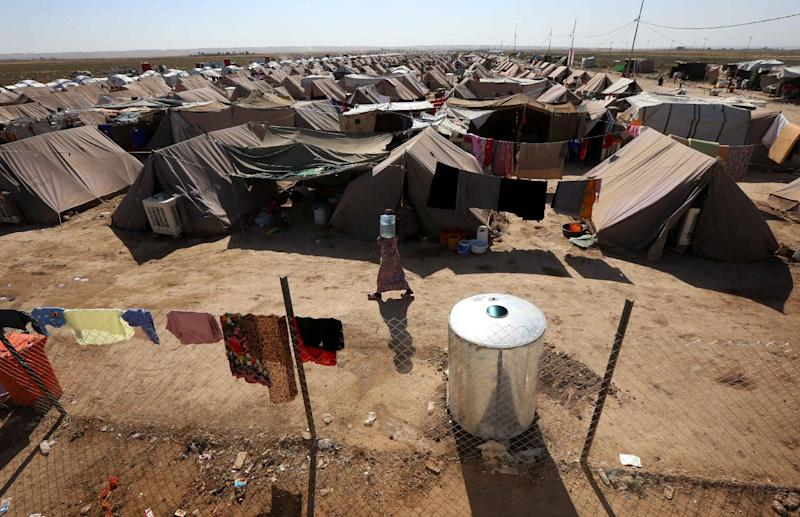 A displaced Iraqi woman carries a container of water at the Ayden camp, an extension of Aliama camp, in Khanaqin, 160 km northeast of Baghdad, on September 27, 2014 (AFP Photo/Safin Hamed)