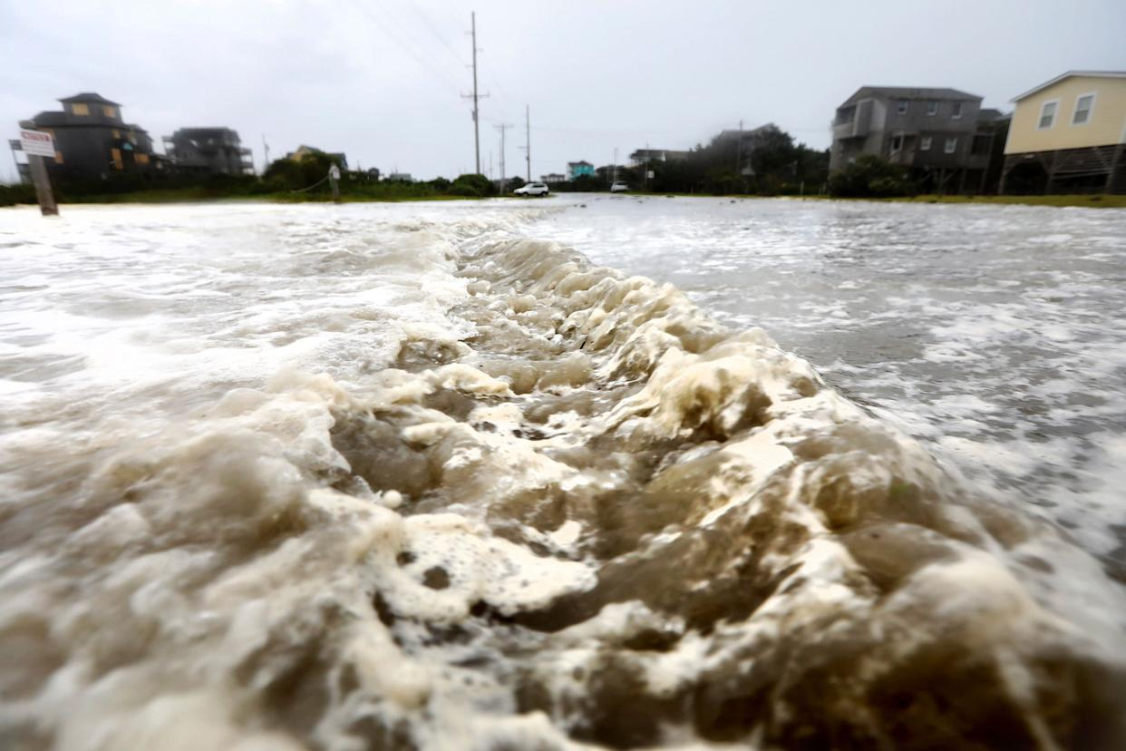 Ocean water breaches the dune line and rushes down Highway 12 in Frisco on Thursday.