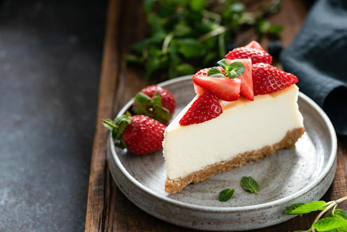 A slice of cheesecake on a plate topped with sliced strawberries and a sprig of mint, two strawberries and mint leaves on the side, all on a wooden plant with mint and a cloth napkin in the background