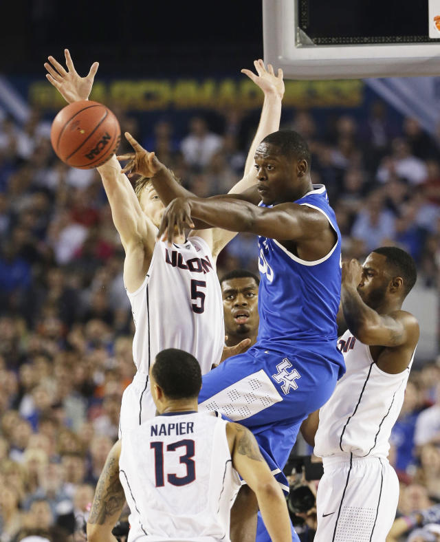 Kentucky forward Julius Randle (30) passes the ball against Connecticut guard Niels Giffey (5) and guard Shabazz Napier (13) during the first half of the NCAA Final Four tournament college basketball championship game Monday, April 7, 2014, in Arlington, Texas. (AP Photo/David J. Phillip)