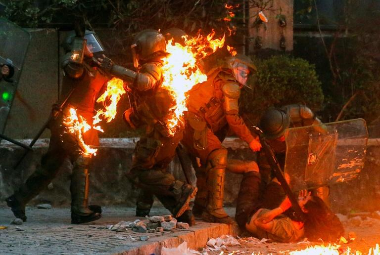 A demonstrator is held while a petrol bomb hits riot police during a protest against the government in Santiago on Friday
