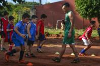 """Defender Jose """"Ruli"""" Rios, of the Fulgencio Yegros Club, second division, trains children from his neighborhood in Ypane, Paraguay, Saturday, Jan. 30, 2021. A professional since age 18, the 35-year-old defender helped four clubs reach Paraguay's first division. To survive during during the COVID-19 pandemic, Rios is working as a gardener as he waits for the 2021 season to begin. (AP Photo/Jorge Saenz)"""