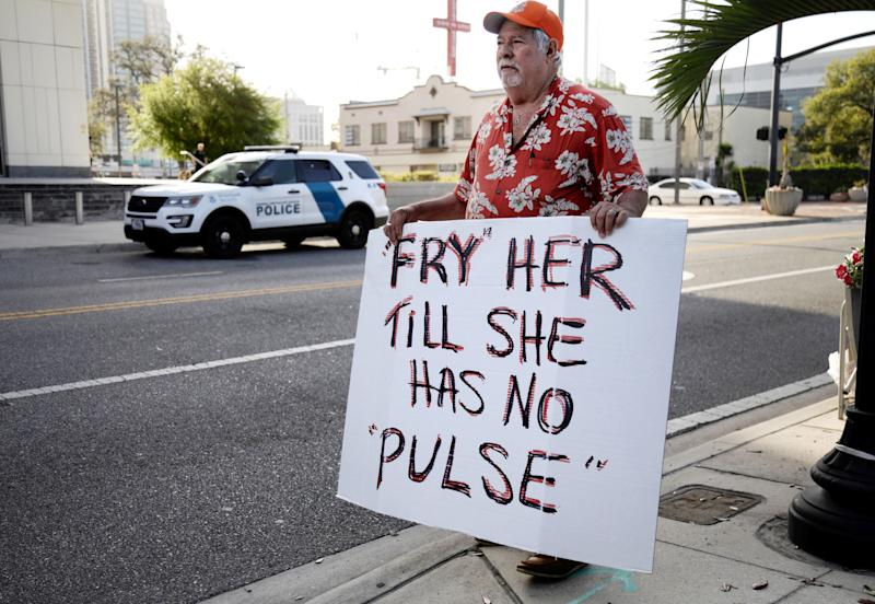 A man protests against Noor Salman, the widow of the Pulse nightclub shooter. Salman is accused of aiding her husband in killing 49 people.