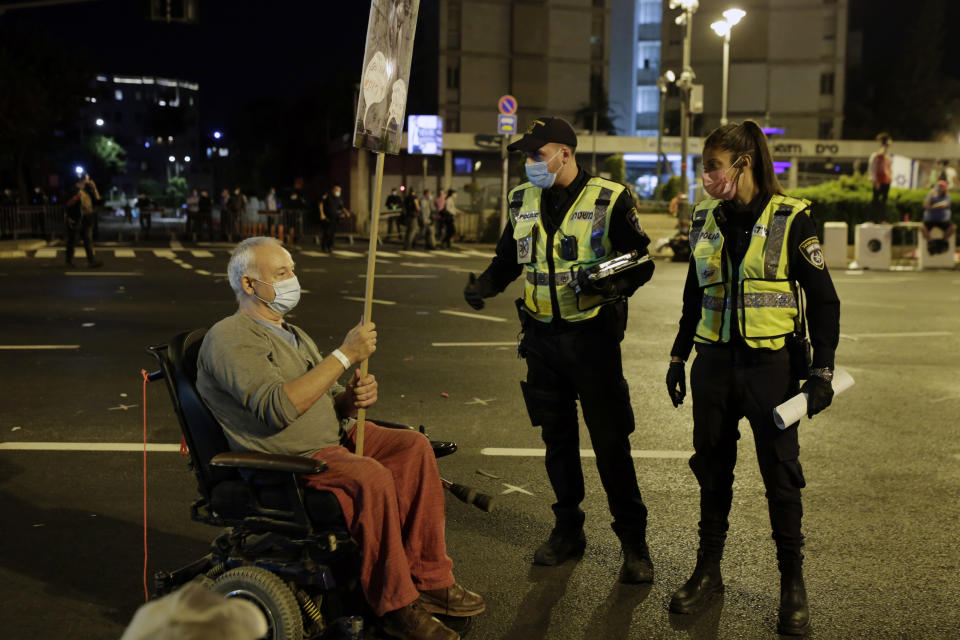 Police ask a protester in a wheelchair to move after security personnel forcibly cleared the square outside of Prime Minister Benjamin Netanyahu's residence in Jerusalem, early Sunday, Sept. 27, 2020, during a three-week nationwide lockdown in Israel to curb the spread of the coronavirus. (AP Photo/Maya Alleruzzo)