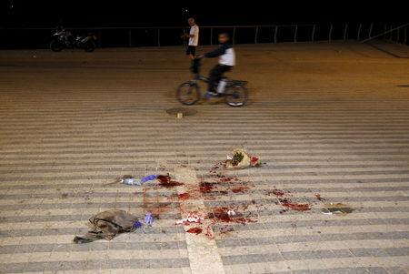 A boy rides past blood stains where, according to Israeli police spokesperson, at least 10 Israelis were stabbed, in the popular Jaffa port area of Tel Aviv, Israel March 8, 2016. REUTERS/Amir Cohen