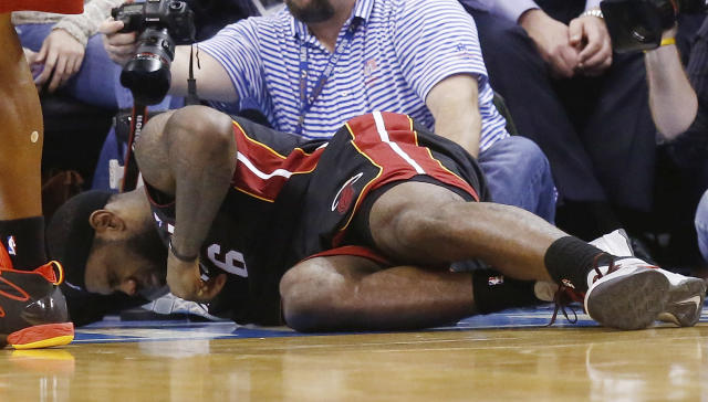 Miami Heat forward LeBron James grimaces as he lies on the floor with a bloody nose in the fourth quarter of an NBA basketball game against the Oklahoma City Thunder in Oklahoma City, Thursday, Feb. 20, 2014. James was struck by Thunder's Serge Ibaka on a drive to the basket. Miami won 103-81. (AP Photo/Sue Ogrocki)