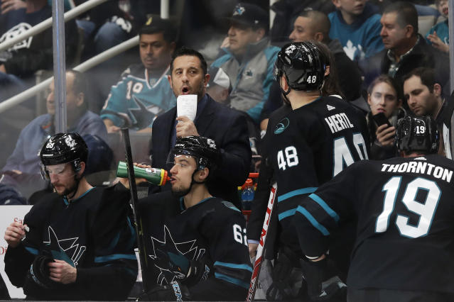 San Jose Sharks interim coach Bob Boughner, center facing, talks to players during the first period of an NHL hockey game against the Vancouver Canucks in San Jose, Calif., Saturday, Dec. 14, 2019. (AP Photo/Jeff Chiu)