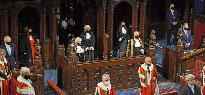 Britain's Prime Minister Boris Johnson, left, Black Rod Sarah Clarke, Speaker of the House of Commons Sir Lindsay Hoyle and Leader of the Opposition Kier Starmer, right, listen as Queen Elizabeth II delivers a speech in the House of Lords at the Palace of Westminster in London, Tuesday May 11, 2021. (Aaron Chown/Pool via AP)