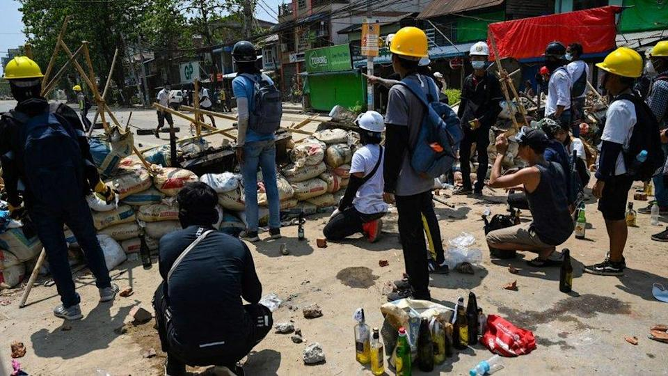 Protesters against the coup in Myanmar at barricades in Yangon's Thaketa township on Friday