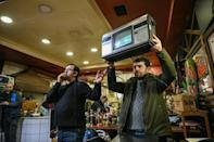 An auctioneer shows items to punters who are as much as anything looking to enjoy a social activity -- even if inflation has trimmed their purchasing power