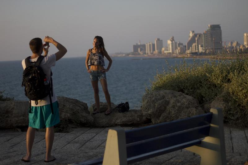 In this picture taken on Friday, Aug. 10, 2012 , a woman pose for a photograph in a spot overlooking the Mediterranean from Jaffa , a mixed Jewish and Arab part of Tel Aviv, Israel. Israel is facing a possible showdown with Iran over its suspect nuclear program, worrying about neighboring Syria's bloody civil war spilling across the border and dealing with armed militants trying to infiltrate from Egypt's lawless Sinai Peninsula. But that doesn't seem to be deterring hundreds of thousands of tourists from flocking to Israel each month. Despite the region's turmoil, Israel is enjoying an unexpected tourism boom, and 2012 is shaping up to be a record year. (AP Photo/Ariel Schalit)
