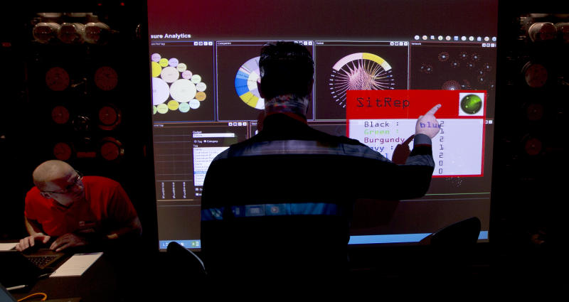 A representative of GCHQ points to a screen showing all the teams progress in completing the task during a mock cyberattack scenario with teams of amateur computer experts taking part and trying to fight this simulated attack in London, Friday, March, 14, 2014. GCHQ is the British Government's electronic intelligence service, they describe themselves as the technical partner to the intelligence and security services, MI6 and MI5. (AP Photo/Alastair Grant)
