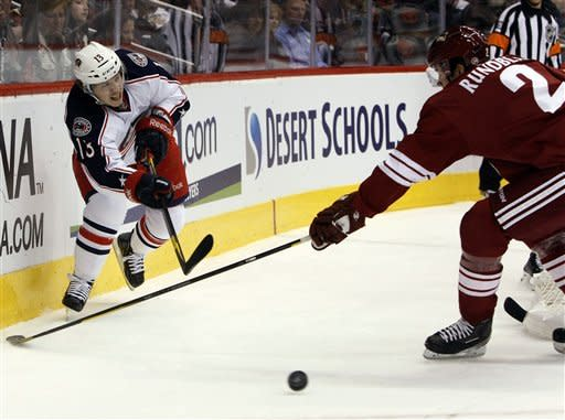 Columbus Blue Jackets right wing Cam Atkinson, left, centers the puck in front of Phoenix Coyotes defenseman David Rundblad in the first period during an NHL hockey game on Saturday, March 3, 2012, in Glendale, Ariz. (AP Photo/Rick Scuteri)