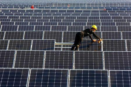 FILE PHOTO: A man works on solar panels at a solar power plant of China Huaneng Group in Huaiyin, Jiangsu province, China June 13, 2018. REUTERS/Stringer/File Photo