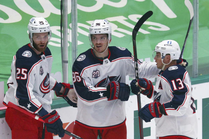Columbus Blue Jackets center Mikhail Grigorenko (25), center Jack Roslovic (96) and right wing Cam Atkinson (13) celebrate a first-period goal against the Dallas Stars during an NHL hockey game Thursday, April 15, 2021, in Dallas. (AP Photo/Richard W. Rodriguez)