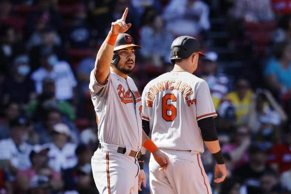 Baltimore Orioles' Anthony Santander signals after scoring with Ryan Mountcastle (6) on a single by Austin Hays during the third inning of a baseball game against the Boston Red Sox, Sunday, Sept. 19, 2021, in Boston. (AP Photo/Michael Dwyer)