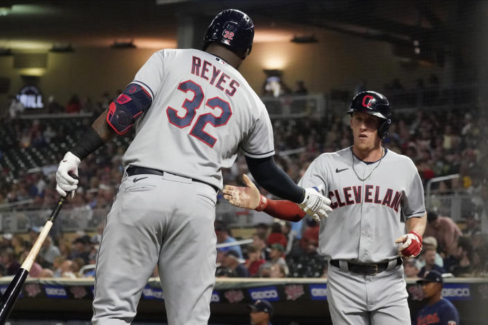 Cleveland Indians' Myles Straw right is congratulated by Franmil Reyes after scoring on a sacrifice fly by Jose Ramirez during the fifth inning of the team's baseball game against the Minnesota Twins on Wednesday, Sept. 15, 2021, in Minneapolis. (AP Photo/Jim Mone)