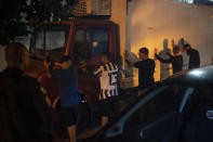 People arriving for a party are checked by police officers during an operation against COVID-19 restriction violations in Rio de Janeiro, Brazil, late Saturday, April 3, 2021. (AP Photo/Felipe Dana)