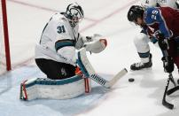 San Jose Sharks goaltender Martin Jones, left, makes a stick save of a shot by Colorado Avalanche center Nathan MacKinnon in the first period of Game 3 of an NHL hockey second-round playoff series Tuesday, April 30, 2019, in Denver. (AP Photo/David Zalubowski)